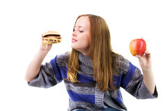 Hungry girl. Chooses between sandwiches and an apple, isolated on white Royalty Free Stock Image