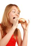 Hungry girl. Young girl eating hamburger, isolated on white royalty free stock photo