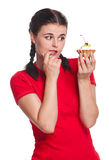 Hungry girl. Looks at a cake isolated on white background Royalty Free Stock Image