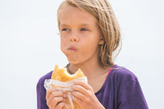 Hungry girl with an appetite chews delicious cake on the beach. A hungry girl with an appetite chews delicious cake on the beach Royalty Free Stock Photography