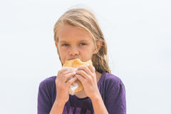 Hungry girl with an appetite chews delicious cake and looked into the frame. A hungry girl with an appetite chews delicious cake and looked into the frame Stock Image