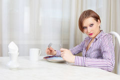 Hungry girl in cafe Stock Images