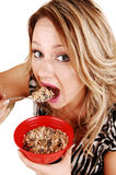 Hungry girl eating. A very hungry young woman eating her breakfast from a red bowl Stock Photo