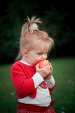 Hungry girl eating apple Stock Image