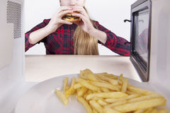 Hungry girl eats a hamburger while sitting at table. View through microwave Stock Photo