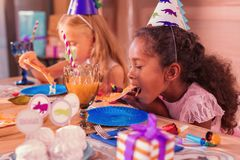 Hungry girl opening her mouth and eating delicious pizza. Eating. Calm hungry long haired girl sitting at the birthday party and eating delicious pizza royalty free stock photo