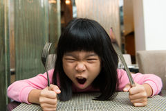 Hungry girl waiting for food. Little Asian girl waiting at table screaming for food Stock Images