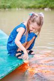 Hungry gold asian fish eats food from bottle in the pond. little beautiful girl feeds fish royalty free stock photo