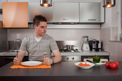 Hungry guy. Sitting in kitchen and waiting for food Royalty Free Stock Photography