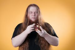A hungry guy in the studio on a yellow background. stock photography