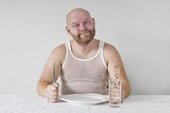 Hungry and Happy Man. With no food on his plate. Perphas on a diet Royalty Free Stock Images