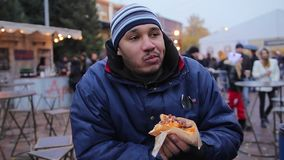 Hungry homeless man eating hot dog outdoors, feeling happy, charity event. Stock footage stock footage