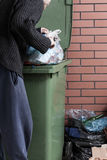 Hungry homeless man looking for food in a dumpster Royalty Free Stock Image
