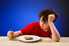Hungry kid. Hungry boy on blue background Royalty Free Stock Image