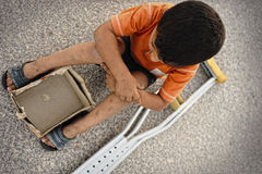 Hungry kid begging  with a crutches beside Stock Images