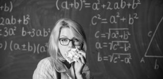 Hungry for knowledge. Teacher ready to eat her paperwork. Teacher eats piece of paper absorb information. Woman teacher. Eats crumpled piece of paper chalkboard stock photography