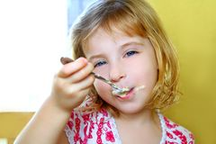 Hungry little blond girl spoon eating ice cream Royalty Free Stock Images