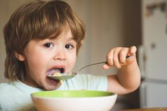 Hungry little boy eating. Cheerful baby child eats food itself with spoon. Tasty kids breakfast. Baby eating food on royalty free stock photography