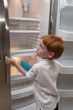 Hungry little boy looking into empty fridge Stock Image