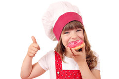 Hungry little girl cook eat donuts Royalty Free Stock Image