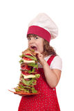 Hungry little girl cook eat sandwich. Hungry little girl cook eat large sandwich Stock Photo