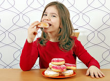 Hungry little girl eat donuts Stock Image