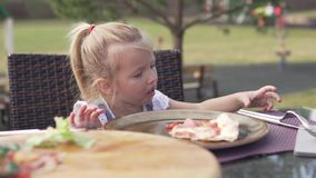 Hungry little girl eating pizza in a cafe on the street on a hot summer day stock footage