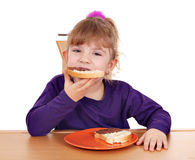 Hungry little girl eats bread Stock Image