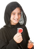 Hungry Little Goblin. Little boy dressed in his halloween costume, looking hungrily at a lollipop. Isolated on white royalty free stock photo