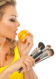 Hungry makeup professional. Gorgeous female holding a peach in one hand and makeup brushes in other Stock Photography