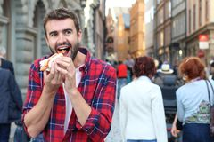 Hungry male devouring a hot dog.  stock image