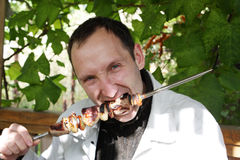 Hungry man. The hungry man bites off a shish kebab piece Stock Photography