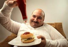 Hungry man. Man sropping sauce on hamburger Royalty Free Stock Photos