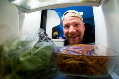 Hungry Man. Photo of a man taken from the inside of a refrigerator Royalty Free Stock Photography