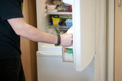 Hungry man. A young man charging in the fridge to find something to eat Stock Photography