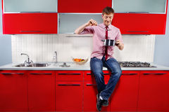 Hungry man. Portrait of  young hungry man filching  pan with soup on red kitchen Royalty Free Stock Photography