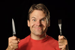 Hungry man. Closeup of hungry Caucasian man in red shirt holding knife and fork on black background while making silly face Stock Photo