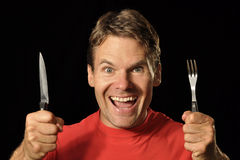 Hungry man. Handsome hungry Caucasian man holds knife and fork while making excited face on black background Royalty Free Stock Photo