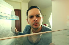 Hungry man closeup. Hungry man with funny face opens the fridge Stock Photography