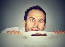 Hungry man craving sweet food. Hungry young man craving sweet food Royalty Free Stock Image