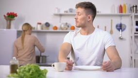 Hungry man eagerly waiting for dinner, wife cooking on background, starvation. Stock footage stock footage
