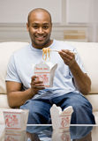 Hungry man eating chinese take-out food. With chopsticks in livingroom Royalty Free Stock Photography