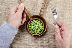 Hungry man eating green peas Royalty Free Stock Photography