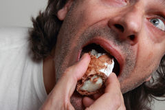 Hungry man eating pastry Royalty Free Stock Photography