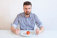 Hungry man feeling angry in front of a dish with a cabbage. Man on diet feeling hungry and forced to eat vegetable meal Stock Photography