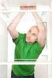 Hungry man in fridge. A hungry man leans on a shelf looking for food in an empty fridge Royalty Free Stock Photos