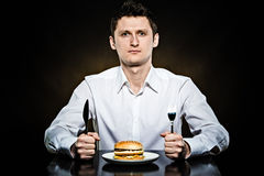 Hungry man is going to eat a burger. Hungry man in the white shirt is going to eat a burger Stock Photography