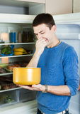 Hungry man holding his nose. Because of bad smell from food near refrigerator at home royalty free stock image