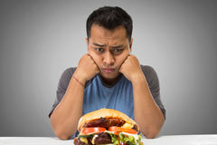 Hungry man looking at big hamburger Royalty Free Stock Images