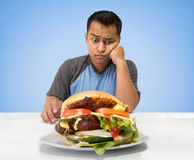 Hungry man looking at big hamburger Stock Photography
